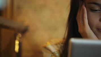 sorridente bella giovane donna adulta seduta sul divano con tablet pc, guardando l'immagine sul tablet, forma orizzontale, social network vista frontale, foto, video