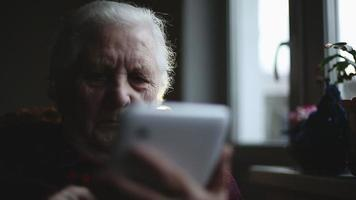 Old woman and electronic tablet. Close up video