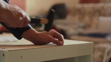 man assembles parts of furniture using a hammer