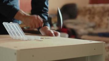 El hombre ensambla partes de muebles con un martillo. video