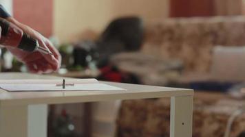 homem monta móveis usando uma chave de fenda elétrica