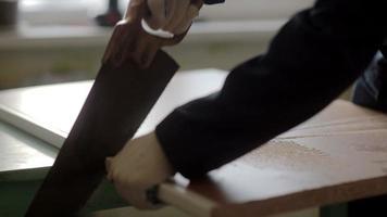 trabalhador masculino usando a serra manual. montagem de móveis