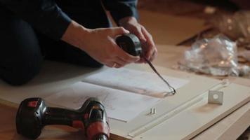 hombre trabajador ensambla muebles usando instrucción video