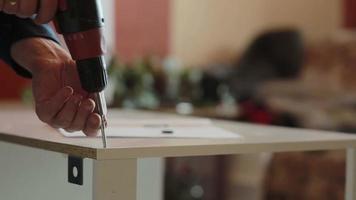 El hombre ensambla los muebles con un destornillador eléctrico
