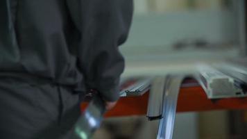 trabalhador coloca cinto flexível em estrutura especial