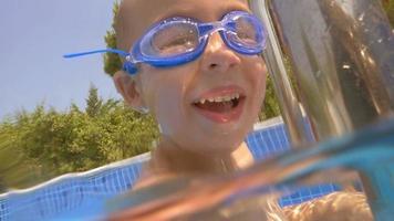 Kind, das eine Schutzbrille trägt, die im Pool taucht