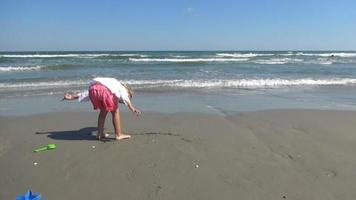 Kind spielt und springt am Strand