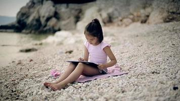 niño se sienta cerca del mar adriático y hace un dibujo video