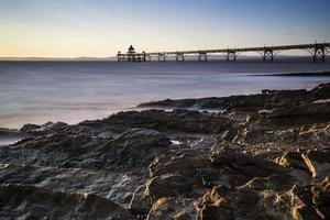 Long exposure landscape image of pier at sunset in Summer photo