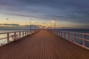 cais de madeira à beira-mar iluminado por lâmpadas elegantes à noite