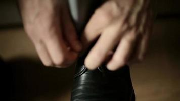 Man putting on his leather shoes