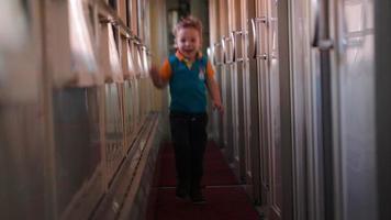 glücklicher Junge, der den Zugflur entlang läuft