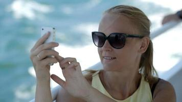 Woman making selfie with smatphone on the boat video