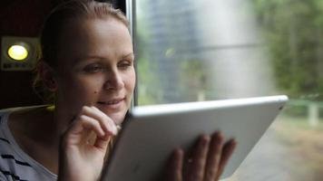 Young woman using touch pad sitting by the window in