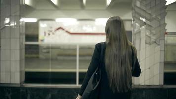 garota esperando o trem do metrô e entra a bordo
