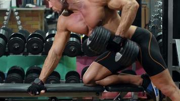 Muscular sportsman doing exercises on left hand with dumbbell in the gym video