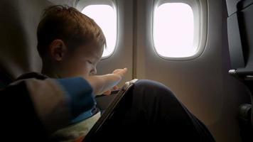 kleiner Junge spielt auf Touchpad im Flugzeug