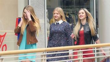 Mädchen gehen mit und unterhalten sich gleichzeitig beim Einkaufen. Nahansicht. Zeitlupe