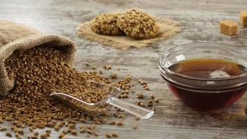 saco de trigo, mel, biscoitos e pão fresco em uma mesa de madeira rústica. café da manhã no campo