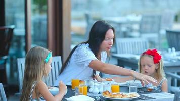 Young mother and adorable little girls having breakfast at outdoor cafe