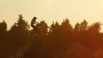 cámara lenta: motocross profesional extremo saltando truco de estilo libre sobre el sol