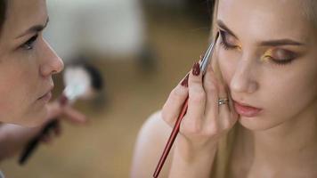 voor sensuele blonde in een schoonheidssalon die make-up doet. benadrukt de ogen met schaduwen video