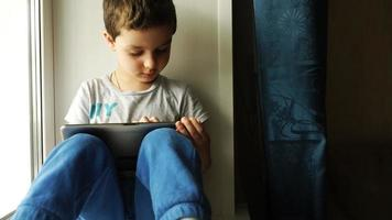 Child sits on a windowsill and uses a tablet pc video