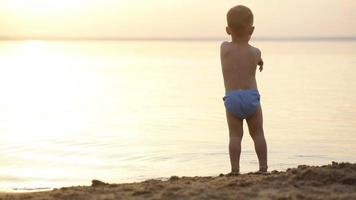 Silhouette of child on the beach, holding his hands up, hugging the sun video