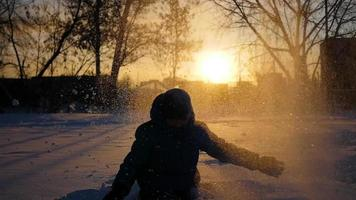 child throwing snow over himself and enjoys it in winter park at sunset