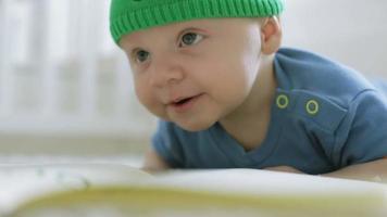 Das dreimonatige Kind schaut in die Kamera, die neben dem Buch auf dem Boden liegt und lächelt.
