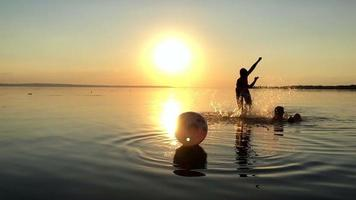 Children playing ball in the water at sunset.