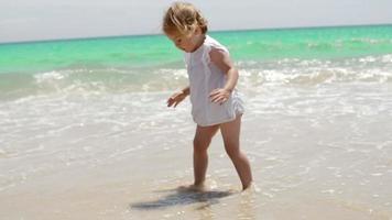adorable petite fille jouant dans les vagues