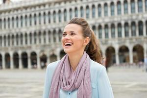 Laughing woman tourist on St. Mark's Square looking up photo