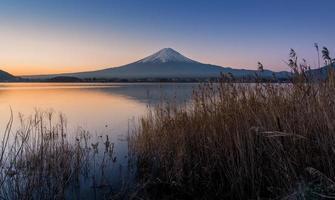 mount Fuji at dawn with peaceful lake