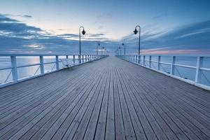 Beautiful long exposure seascape with wooden pier photo