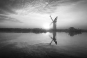 landscape of windmill and river at dawn black and white photo