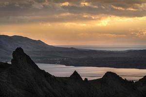 siluetas de montañas al atardecer sobre un fondo nublado foto
