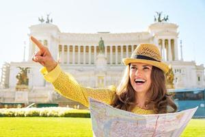 Happy young woman on piazza venezia in rome, italy pointing photo