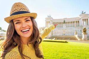 Happy young woman pointing on piazza venezia in rome, italy photo