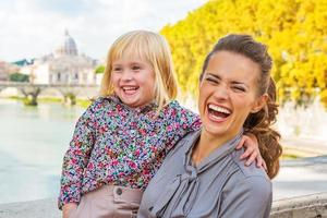 Happy mother and baby girl on bridge ponte umberto I photo