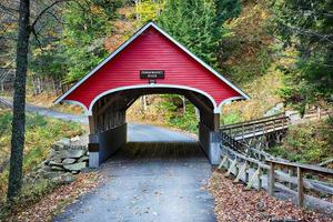 Red covered bridge in New Hampshire during Fall season photo