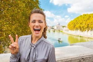 Portrait of happy young woman showing victory gesture in Rome photo
