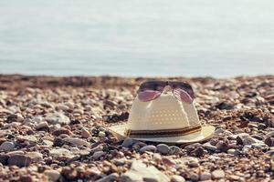 Straw hat and sunglasses on the beach photo