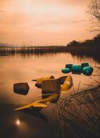 Botes de remo se hunden en el agua durante la puesta de sol