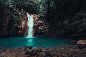 Waterfall cascading into turquoise pond