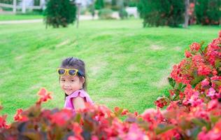 Asian girl in pink dress sitting on the ground in flower garden