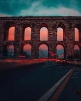 Traffic lights against aged aqueduct at sunset