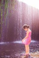 Asian girl playing in the water at a spillway