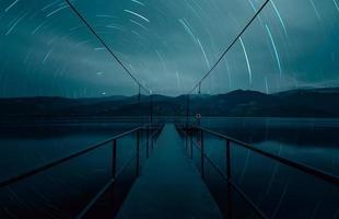 Estelas de estrellas sobre el puente marino en la hora azul