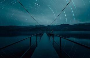 Star trails over seascape bridge at blue hour